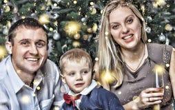 La Navidad del Año Nuevo La familia joven feliz con un pequeño hijo que sonríe feliz resuelve el Año Nuevo en casa Árbol de navid Imagen de archivo