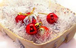 La Navidad del Año Nuevo Juguetes en una cesta, esferas rojas, conos del pino, caramelos dulces de un juguete Foto de archivo libre de regalías