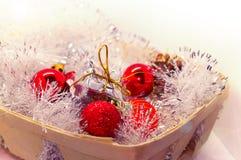 La Navidad del Año Nuevo Juguetes en una cesta, esferas rojas, conos del pino, caramelos dulces de un juguete Imagen de archivo