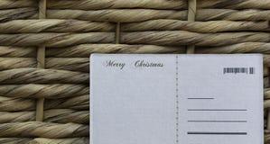 La Navidad desea la postal en un fondo de mimbre Fotos de archivo libres de regalías