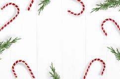 La Navidad diseñó la foto común Fondo de madera blanco con las decoraciones del bastón de caramelo, las ramas imperecederas del J foto de archivo