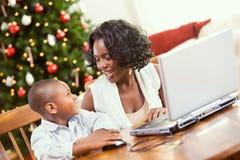La Navidad: El muchacho de ayuda de la madre escribe a Santa Letter On Computer Imágenes de archivo libres de regalías