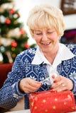 La Navidad: El quitar de la cinta al regalo del sello Foto de archivo libre de regalías