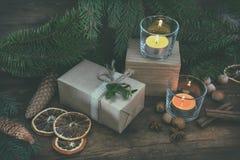 La Navidad empaqueta el regalo y dos velas ligeras Foto de archivo