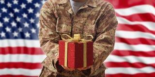 La Navidad en el ejército Bola de la Navidad y caja de regalo en un uniforme militar americano fotografía de archivo