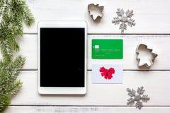 La Navidad en línea de las compras con la opinión superior del fondo de madera de la e-tableta Fotografía de archivo libre de regalías