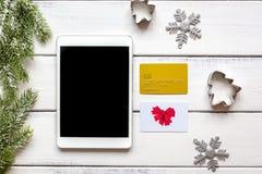 La Navidad en línea de las compras con la opinión superior del fondo de madera de la e-tableta Fotografía de archivo
