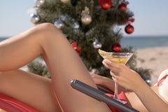 La Navidad en la playa con un cóctel a disposición Fotografía de archivo libre de regalías
