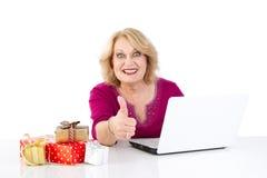 La Navidad en línea de las compras maduras - mujer aislada en el backg blanco Foto de archivo libre de regalías