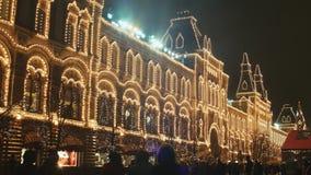 La Navidad en Moscú Iluminación festiva de la ciudad y de los edificios en la noche Transeúntes que caminan Cuadrado rojo Tema de almacen de metraje de vídeo