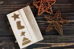 La Navidad envolvió la actual caja y los juguetes de oro de las estrellas en b elegante Imagen de archivo libre de regalías