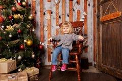 La Navidad hecha en casa, niño que se sienta en vieja trona Fotografía de archivo