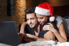 La Navidad joven feliz de los pares que hace compras en línea Fotos de archivo