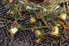La Navidad juega campanas de oro y la malla Fotografía de archivo libre de regalías