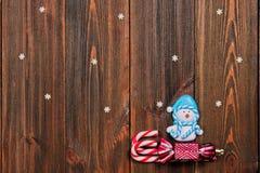 La Navidad juega el muñeco de nieve en un trineo de bastones en TA de madera marrón Imagen de archivo libre de regalías