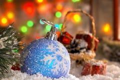 La Navidad juega en la nieve, una linterna roja con una vela, una guirnalda de luces, un bokeh Fotografía de archivo libre de regalías
