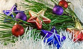 La Navidad juega las estrellas y las bolas en la decoración blanca con la rama del árbol de pino Foto de archivo