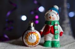 La Navidad juega - un muñeco de nieve y un reloj Imagenes de archivo