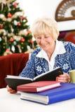 La Navidad: La mujer mayor mira álbumes de foto Fotos de archivo