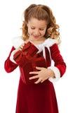 La Navidad: La niña abre la caja de la Navidad Imágenes de archivo libres de regalías
