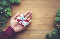La Navidad, los conceptos de la celebración del Año Nuevo con la mano humana que sostiene la caja de regalo presenta Imagen de archivo