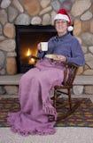 La Navidad mayor de la chimenea de la silla de oscilación de la mujer Imagenes de archivo
