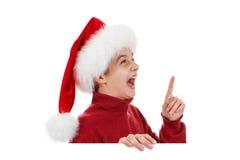 La Navidad, muchacho feliz en el sombrero de Papá Noel que señala el finger Foto de archivo libre de regalías