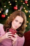 La Navidad: Mujer que se relaja con la bebida caliente Imagen de archivo libre de regalías