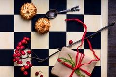 La Navidad o Año Nuevo presente en un tablero de ajedrez con biscu del coco Foto de archivo libre de regalías