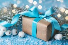 La Navidad o composición del Año Nuevo con la caja de regalo y árbol de abeto nevoso en fondo del bokeh de la turquesa Tarjeta de Fotografía de archivo