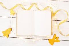La Navidad o composición del marco del Año Nuevo maqueta del libro y de las decoraciones de oro de la Navidad en fondo de madera  Imagen de archivo libre de regalías
