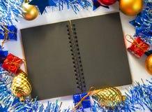 La Navidad o composición plana del Año Nuevo Cuaderno de papel negro con la página en blanco Fotografía de archivo libre de regalías