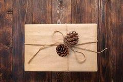 La Navidad o el Año Nuevo presenta la caja de regalo con los conos en una visión superficial blanca caliente natural de madera de Foto de archivo libre de regalías