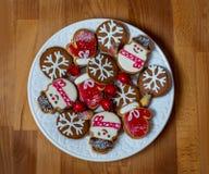 La Navidad o la tarjeta del día de San Valentín adornó las galletas en la placa blanca Galletas del pan de jengibre en fondo de m Imagen de archivo
