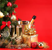 La Navidad o Nochevieja Champán y presentes sobre rojo Fotos de archivo