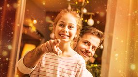 La Navidad - padre e hija que miran hacia fuera la ventana Imagenes de archivo