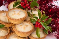 La Navidad pica las empanadas con acebo y decoraciones Imágenes de archivo libres de regalías