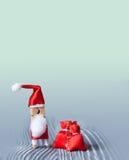 La Navidad, plantilla de la invitación del día de fiesta del Año Nuevo Pinza de Santa Claus Colocación con un bolso rojo del rega Foto de archivo