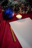 La Navidad. Pluma, papel, vela y bola azul. Fotografía de archivo libre de regalías