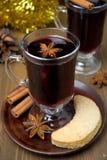 La Navidad reflexionó sobre el vino con las especias en vidrio y galletas Imagenes de archivo