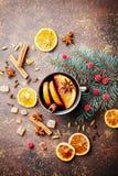 La Navidad reflexionó sobre el vino o el gluhwein con las especias y las rebanadas anaranjadas en la opinión de sobremesa rústica Fotos de archivo