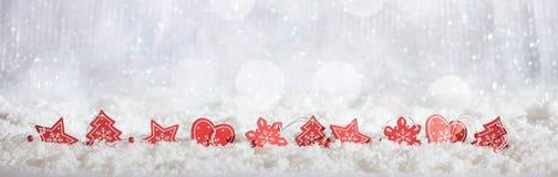 La Navidad roja adorna fila en fondo nevoso del bokeh de la Navidad Foto de archivo