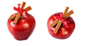 La Navidad roja brillante de las manzanas adornada con los palillos de canela en el fondo blanco Foto de archivo libre de regalías