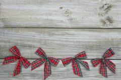La Navidad roja de la tela escocesa arquea el fondo de madera rústico de la frontera Foto de archivo libre de regalías