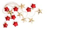 La Navidad roja de las chucherías de las estrellas de oro adorna el fondo blanco Imagen de archivo libre de regalías