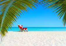 La Navidad Santa Claus que se relaja en sunlounger en la playa tropical arenosa del océano Imagen de archivo