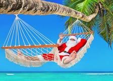 La Navidad Santa Claus que toma el sol en hamaca en el bea tropical de la palma Foto de archivo libre de regalías