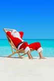 La Navidad Santa Claus se relaja en deckchair en la playa arenosa del océano fotos de archivo libres de regalías