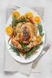 La Navidad tradicional asó la naranja, la zanahoria, y el romero de la guarnición del pollo en la tabla ligera Visión superior Co imágenes de archivo libres de regalías