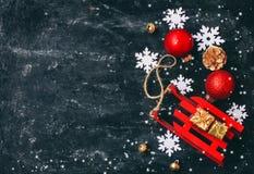 La Navidad, trineo rojo del juguete del fondo del Año Nuevo, bolas, caja de regalo Imagen de archivo libre de regalías